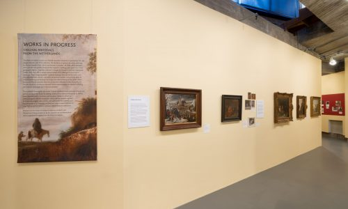 Eye-level view of exhibition intro text wall with oblique view of wall with five paintings and two didactic text panels