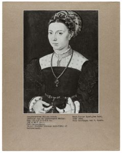 black and white image of a half-length portrait of a woman looking at us in three quarter profile, mounted on tan paper with typewritten caption
