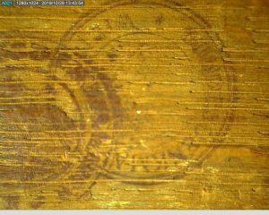 """Detail of a faint circular stamp reading """"Bundesdenkmalamt Wien"""" on the back of a painting's panel support"""