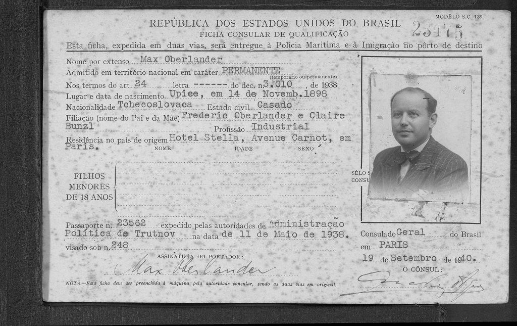 Paper card with typewritten personal information in Portuguese and passport photo of a middle-aged man in three-quarter profile, two signatures toward the bottom