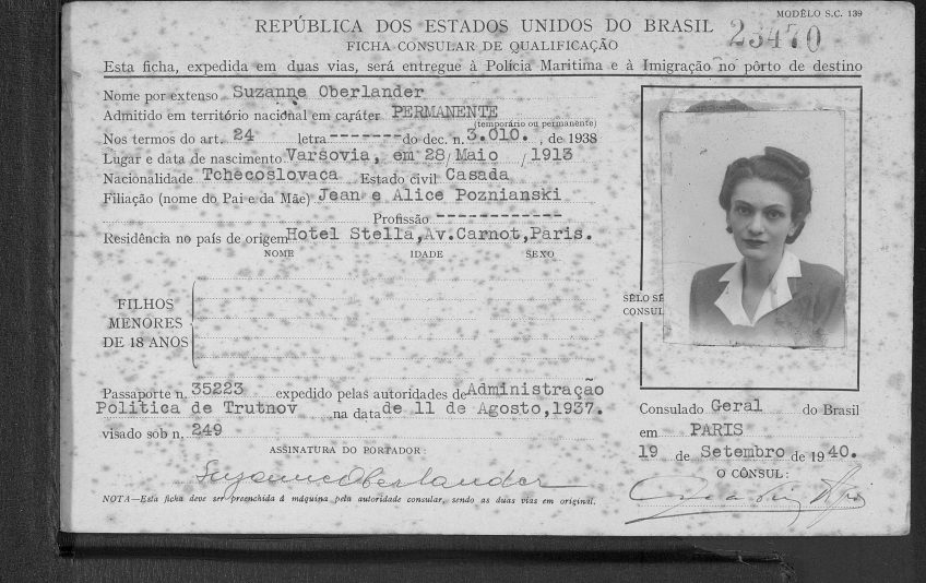 Paper card with typewritten personal information in Portuguese and passport photo of a young woman, two signatures toward the bottom